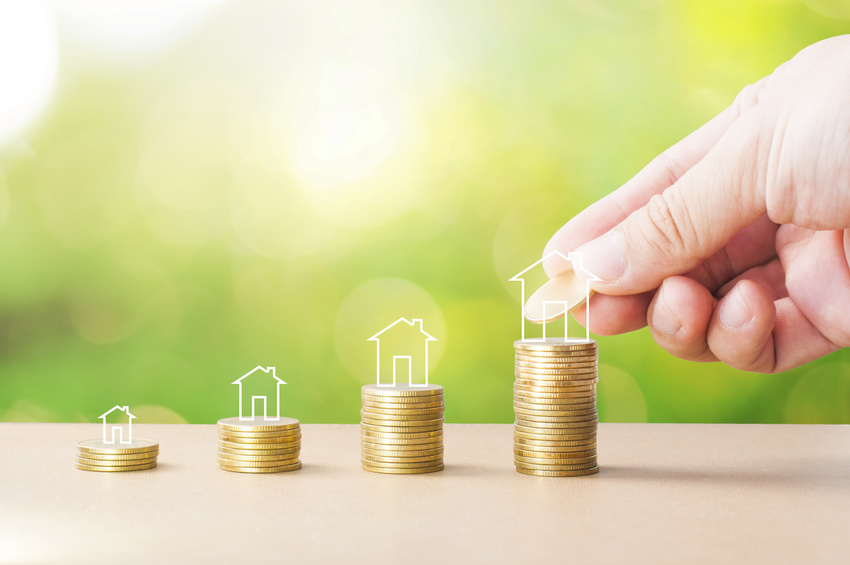 Hand adding coin to stack of golden coins with house icon on wooden table with bokeh green background for growth up saving to buy house, mortgage or home loan concept