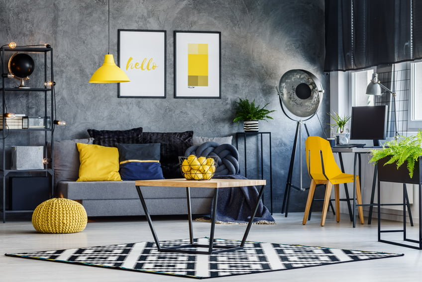 Masculine room decor with yellow lamp, chair, pouf, poster and cushions