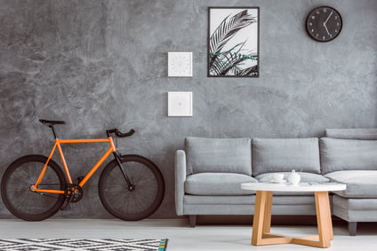 Orange bike next to grey sofa in living room with coffee table,black clock and posters on concrete wall
